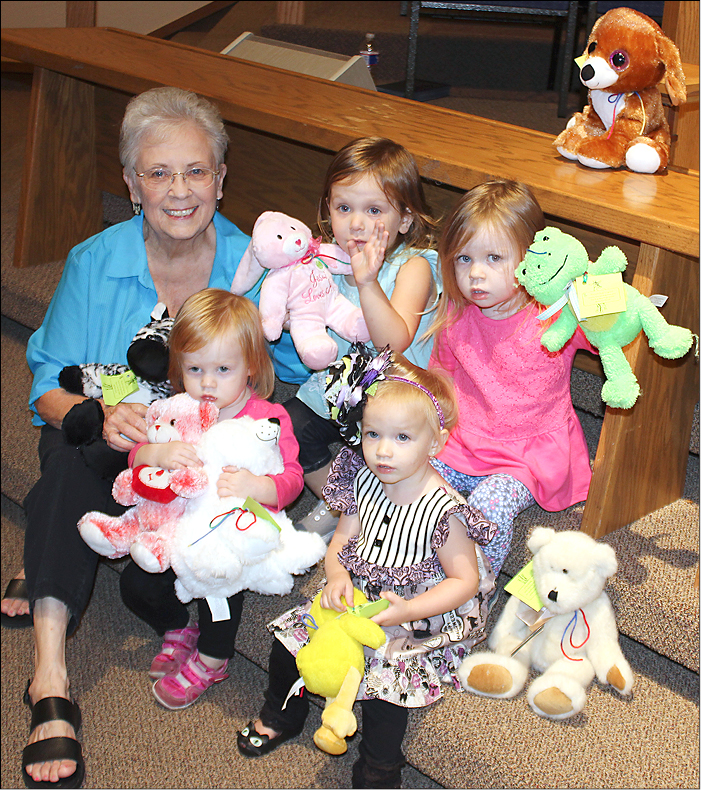 Nellyne Hanlin cuddles toys and kids at OKC-New Hope. Clockwise from her are Rosie Miller, age 2; Rylee Goff, 2; Lydia Langert, 1; and Grace Keimig, 1.